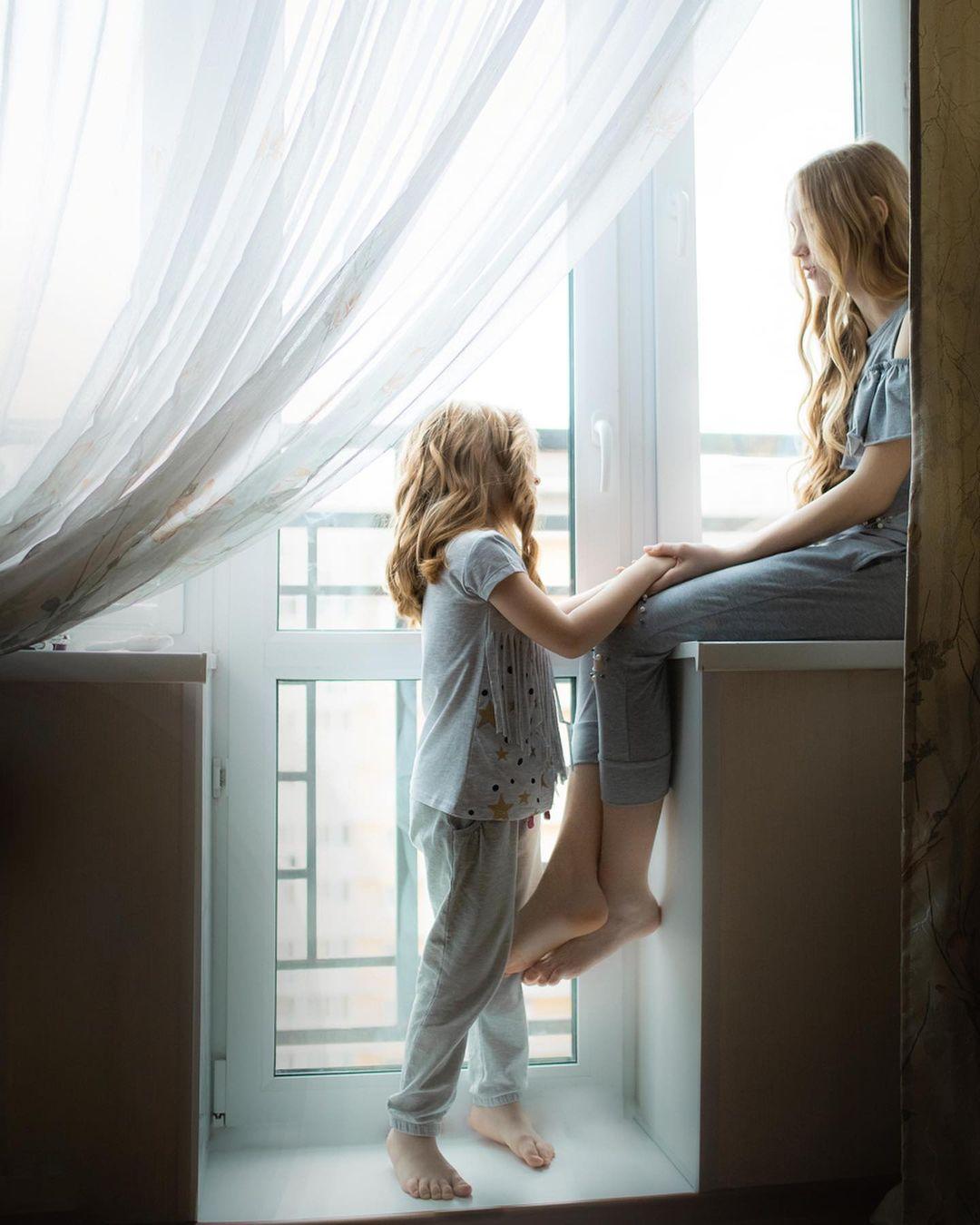 Девочки на домашней фотосессии одеты в серую одежду с неярким узором, и кадр выглядит гармонично